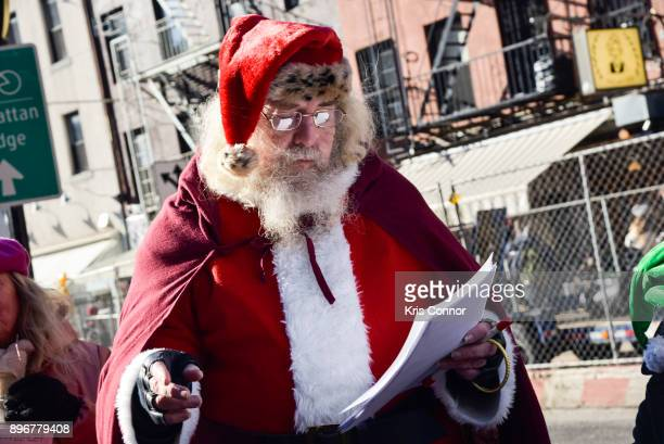 A man playing Santa Claus and members of Earth is Our Mother sing Christmas carols at Petronsino Square as part of 'Make Music Winter December 21' on...