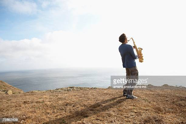 Man playing saxophone on cliff
