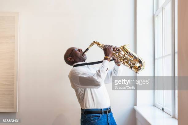 man playing saxophone window - saxophone stock pictures, royalty-free photos & images
