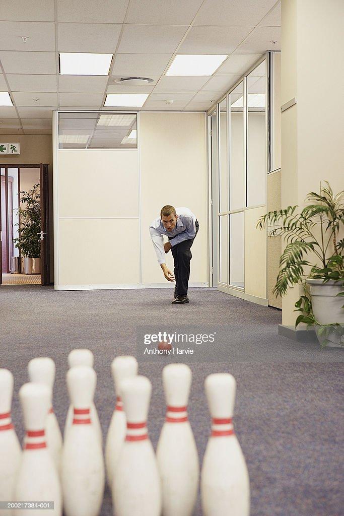 Man playing skittles in office corridor (Focus on man) : Stock-Foto
