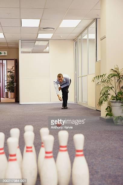 Man playing skittles in office corridor (Focus on man)