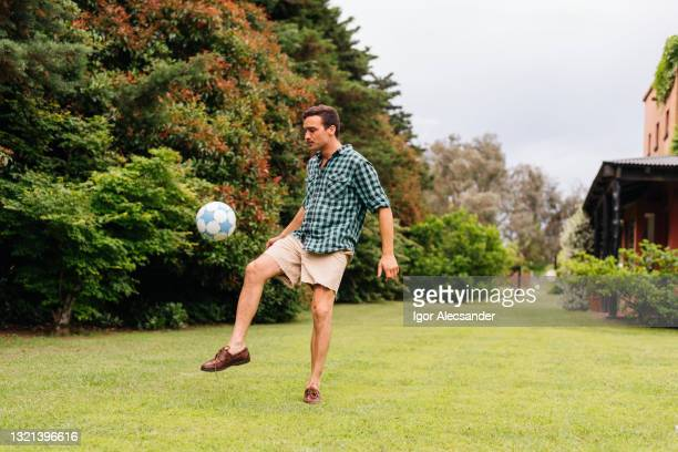 man playing soccer on the backyard lawn - shooting at goal stock pictures, royalty-free photos & images