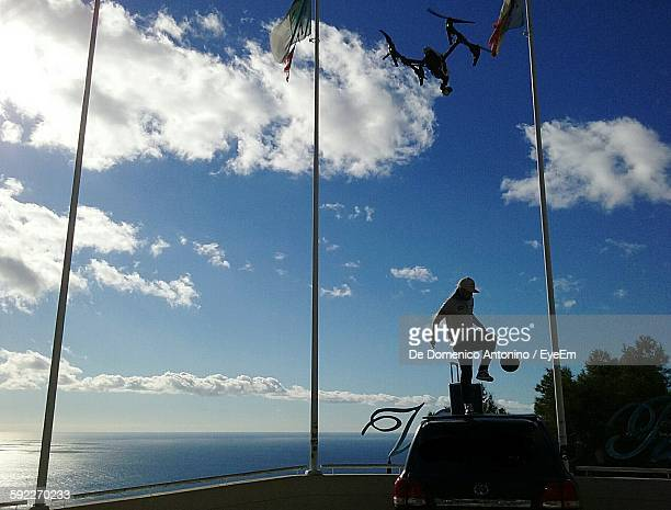 Man Playing Soccer On Top Of Car By Sea Against Sky