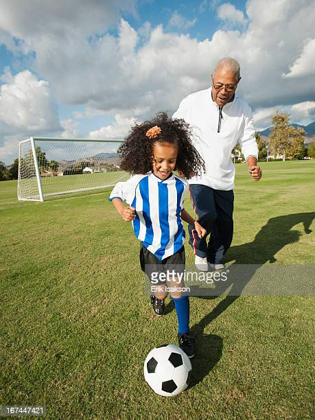 man playing soccer with granddaughter - old american football stock photos and pictures