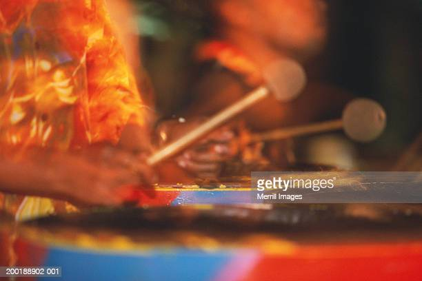 man playing steel drum, close-up (blurred motion) - steel drum stock photos and pictures