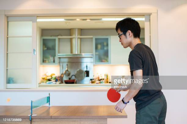 man playing table tennis in his living room - funny ping pong stock pictures, royalty-free photos & images