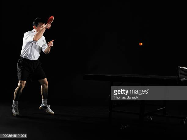 Man playing table tennis, side view