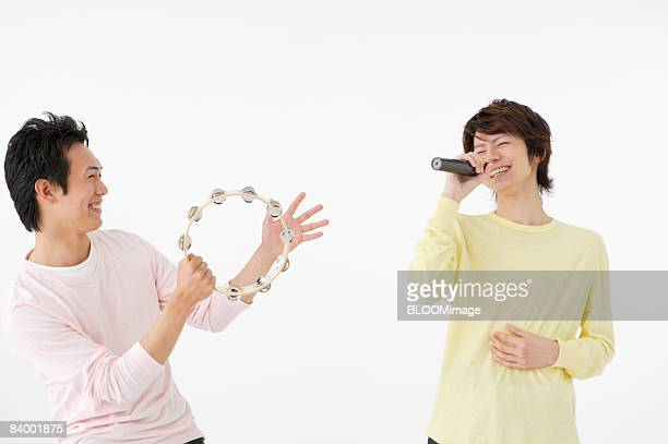 Man playing tambourine and man singing into microphone, studio shot