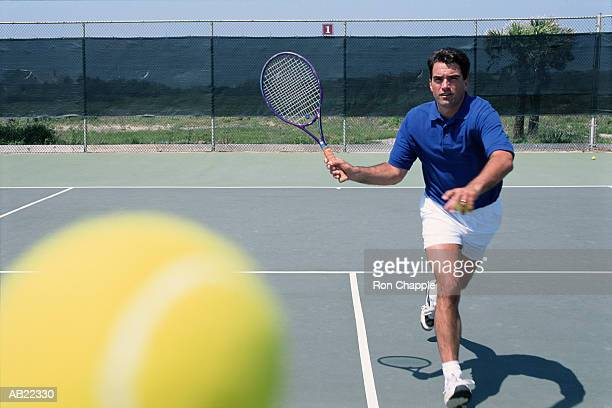 Man playing tennis, ball in foreground
