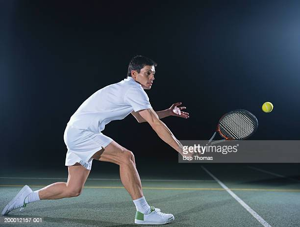 man playing tennis on outdoor court, night - tennis photos et images de collection