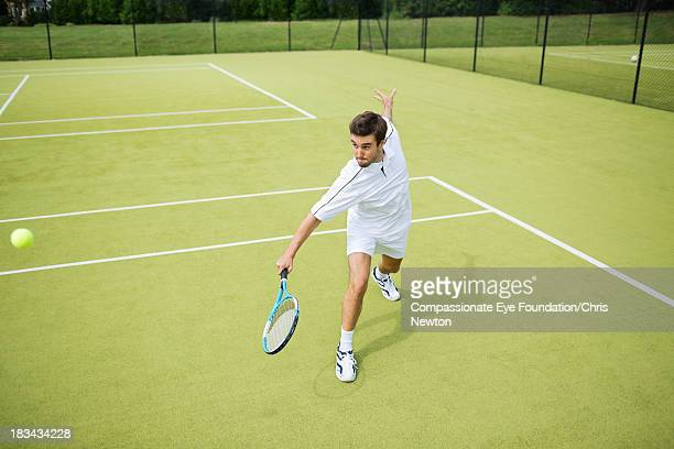 man playing tennis on outside court - tennis stock pictures, royalty-free photos & images