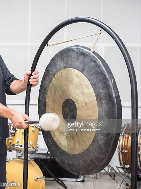 man playing the gong with a mallet - gong stock photos and pictures