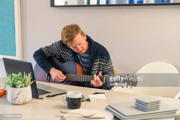 man playing the guitar at home. he is using following an online tutorial - songwriter stock pictures, royalty-free photos & images