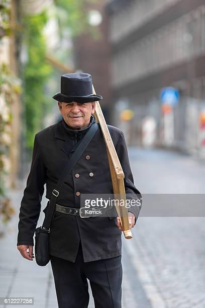 man playing the role of a chimney sweeper - schornsteinfeger stock-fotos und bilder