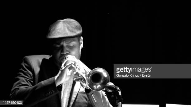 man playing trumpet against black background - krings stock pictures, royalty-free photos & images