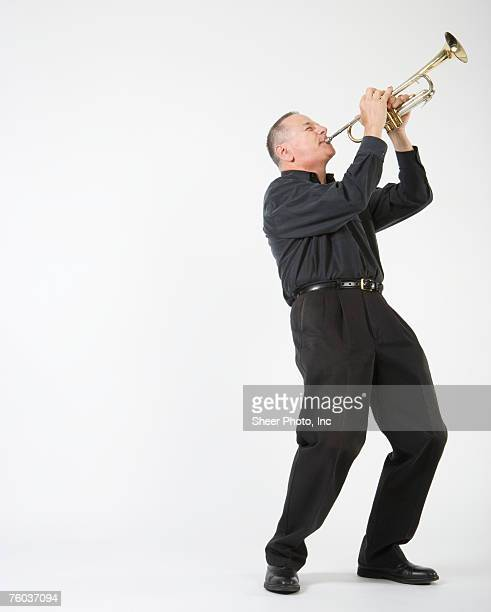 Man playing trumpet, against white background