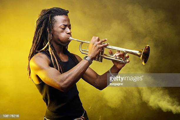 man playing trumpet on stage - trumpet stock photos and pictures