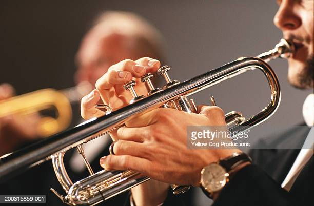man playing trumpet, side view, close-up - orchestra stock pictures, royalty-free photos & images