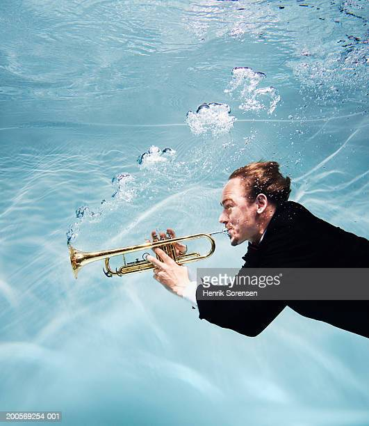 Man playing trumpet underwater, side view