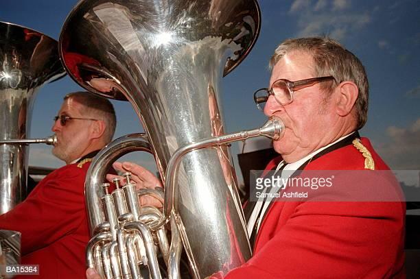 man playing tuba in brass band, close-up - ブラスバンド ストックフォトと画像