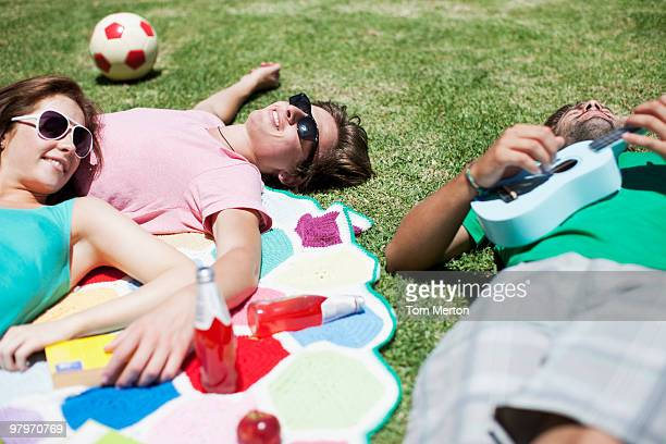 Man playing ukulele for friends laying on blanket in sunny grass