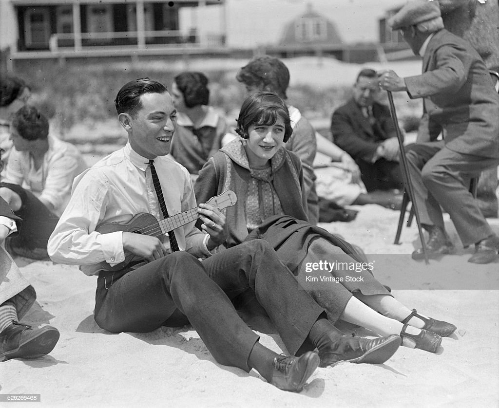 Man playing ukulele for his date at a beach party, ca. 1910