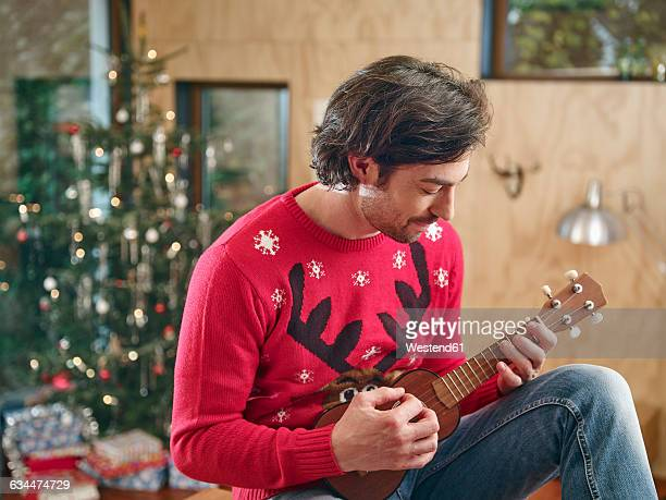 Man playing ukulele in front of Christmas tree