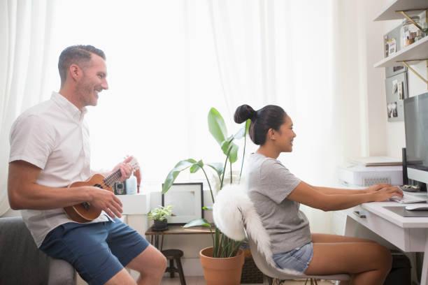 Man playing ukulele watching woman using computer