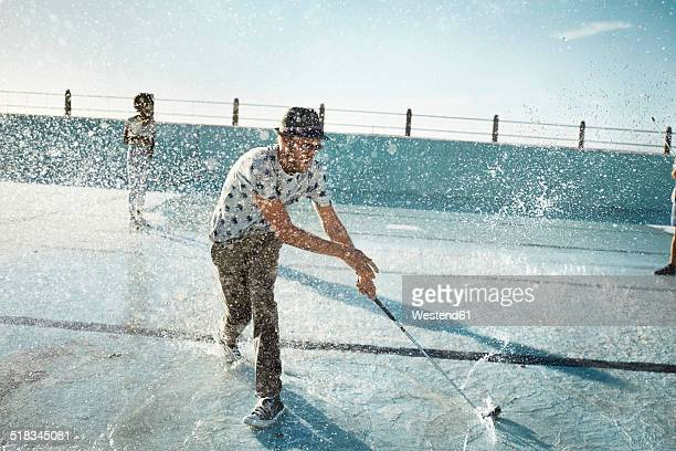 Man playing urban golf in empty swimming pool