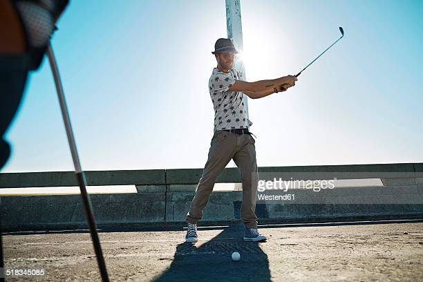 Man playing urban golf on street
