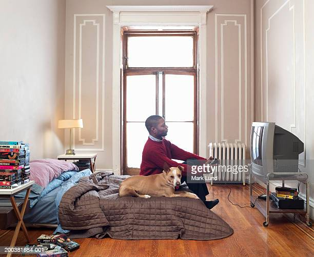 Man playing video game in flat, dog on bed