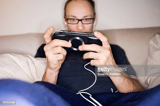 a man playing video game on a psp sweden. - psp stock photos and pictures