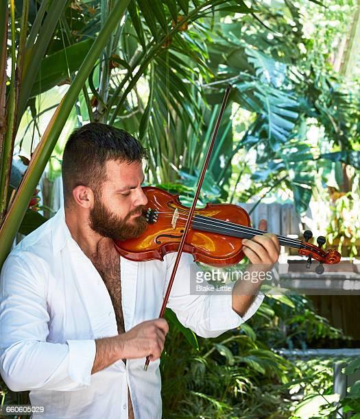 Man playing violin in garden
