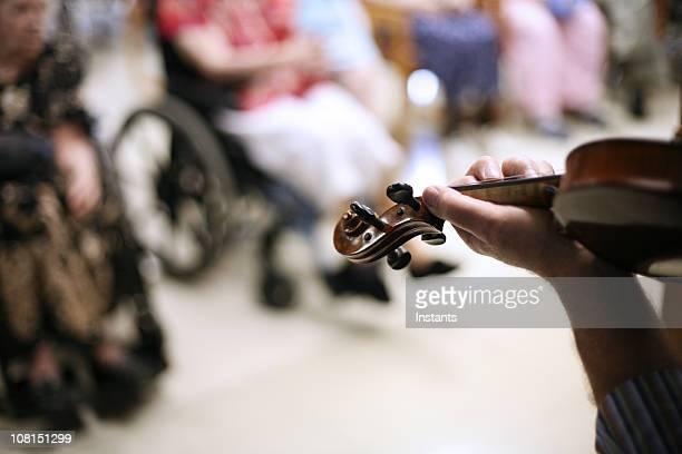 Hombre tocando violín en un asilo de ancianos