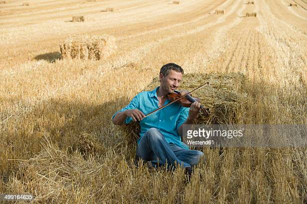 Man playing violin in stubble field