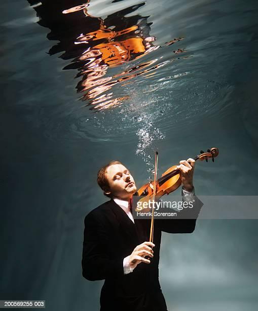 Man playing violin underwater