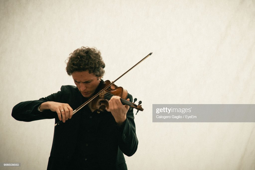 Man Playing Violin While Standing Against Wall : Stock Photo