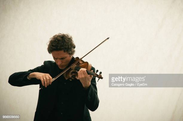 man playing violin while standing against wall - stringed instrument stock pictures, royalty-free photos & images