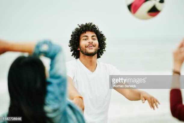Man playing volleyball with friends during beach party