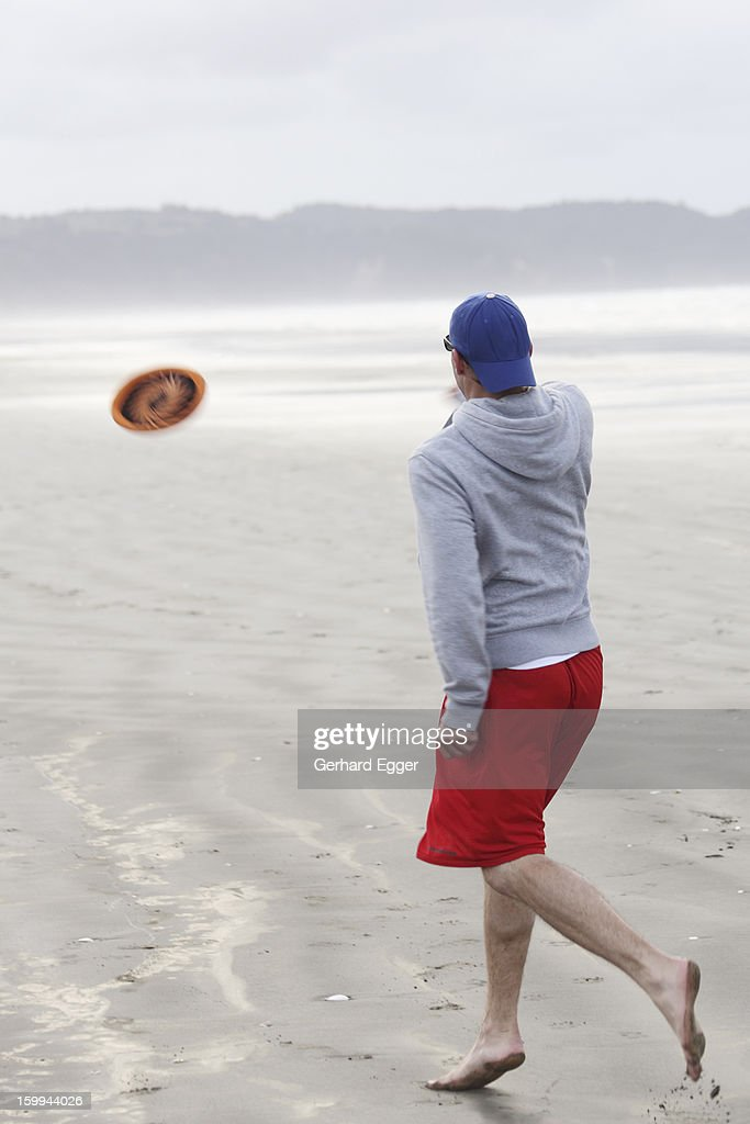 Man playing with a frisbee on beach : Foto de stock