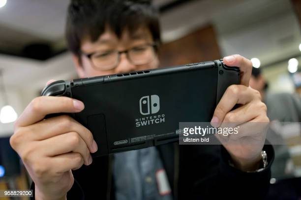 Man playing with a Nintendo Switch video game console.