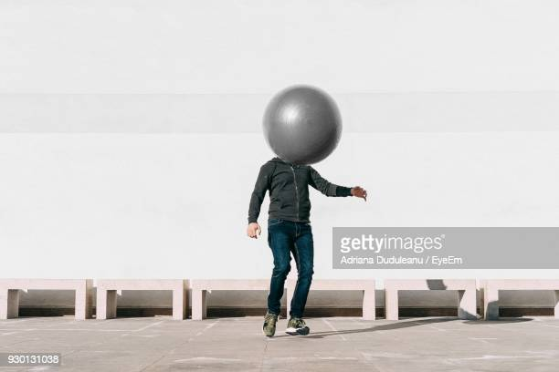 Man Playing With Ball Against Wall