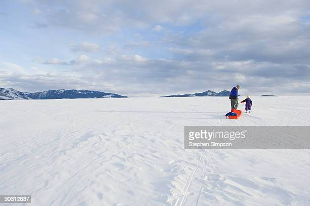 Man playing with children in snow