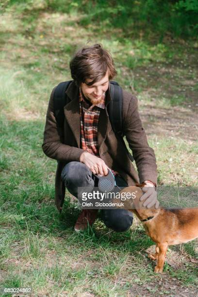 man playing with dachshund dog in park - dachshund holiday stock pictures, royalty-free photos & images