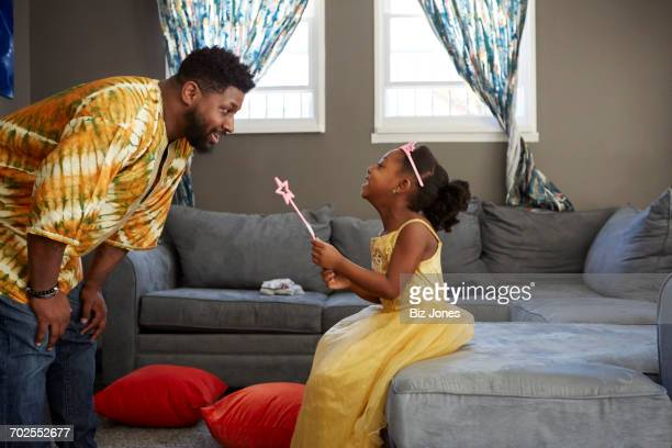 Man playing with daughter in fairy costume in living room