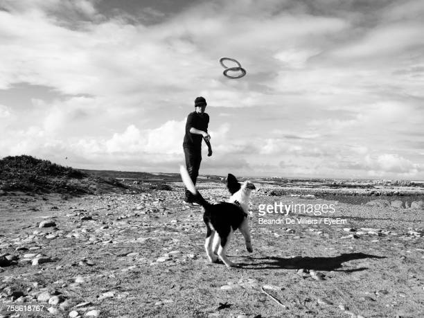 Man Playing With Dog On Field