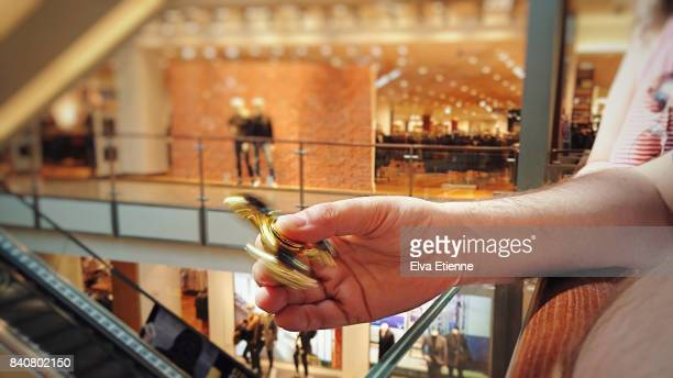 Man playing with fidget spinner in a shopping mall
