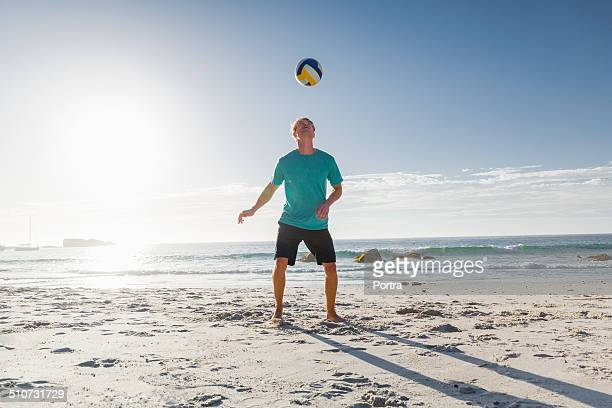 Man playing with football on beach