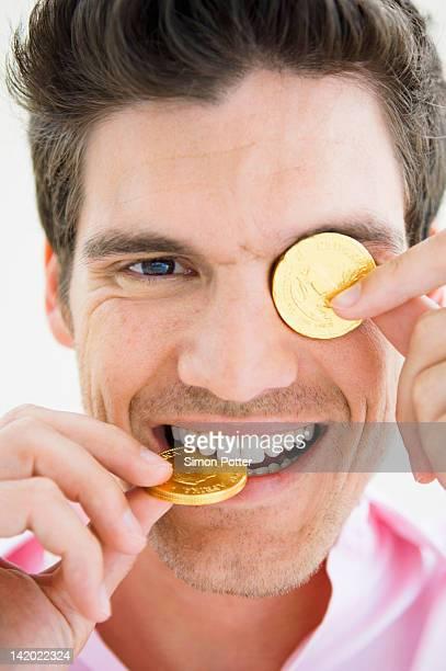 Mann spielt mit gold-Münzen