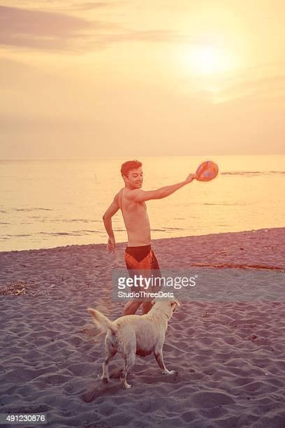 Homme qui joue avec son chien sur la plage